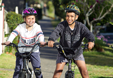 Children and bike program supervisors pose with their Aboriginal motif helmets, showing how they should sit two fingers above the eyebrows.