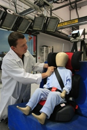 A technician adjusts the seat belt on child dummy.