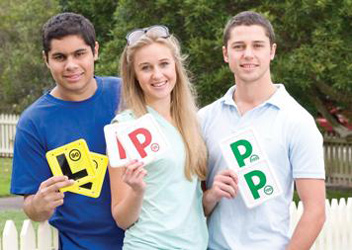 Three smiling young drivers hold up L and P plates.
