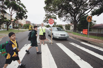 A school crossing supervisor stops traffic to allow two schoolboys to cross the road safely.